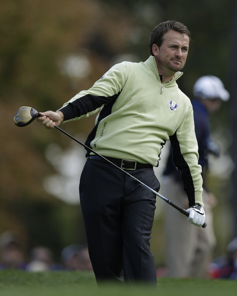 Photo -   Europe's Graeme McDowell reacts after hitting a drive into the water on the 15th hole during a foursomes match at the Ryder Cup PGA golf tournament Friday, Sept. 28, 2012, at the Medinah Country Club in Medinah, Ill. (AP Photo/David J. Phillip)