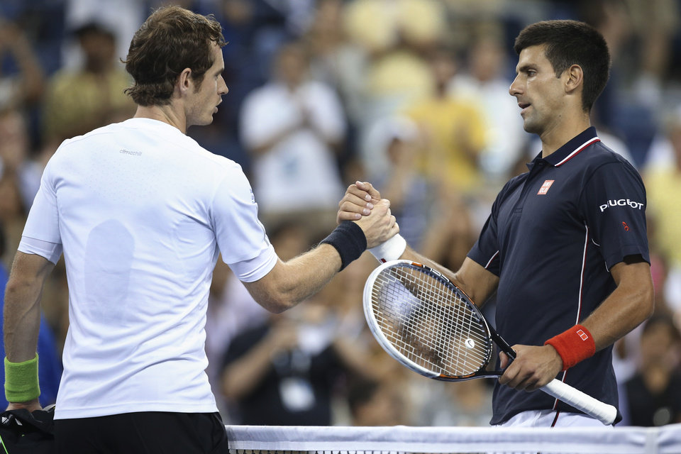 Photo - Novak Djokovic, right, of Serbia, clasps hands with Andy Murray, of Britain, at the net after a quarterfinal of the U.S. Open tennis tournament, early Thursday, Sept. 4, 2014, in New York. Djokovic won 7-6 (1), 6-7 (1), 6-2, 6-4. (AP Photo/John Minchillo)