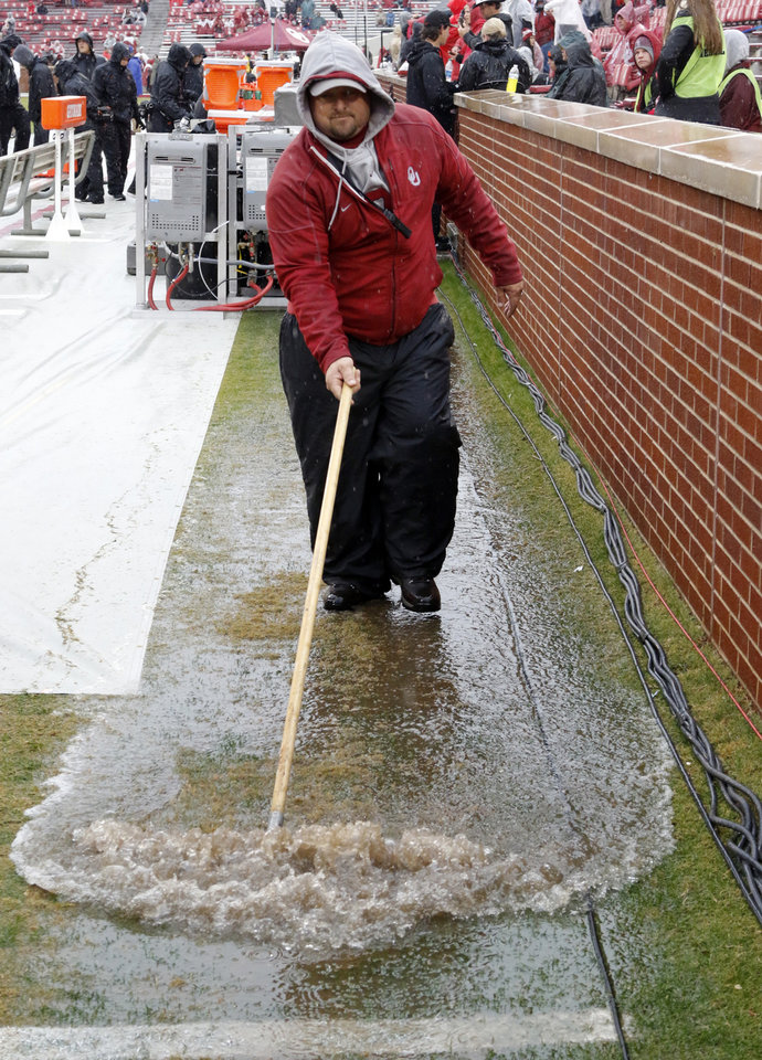 Photo - University of Oklahoma groundskeeper Jeff Salmond pushes water off the sideline before the Bedlam college football game between the Oklahoma Sooners (OU) and the Oklahoma State Cowboys (OSU) at Gaylord Family - Oklahoma Memorial Stadium in Norman, Okla., Saturday, Dec. 3, 2016. Photo by Steve Sisney, The Oklahoman