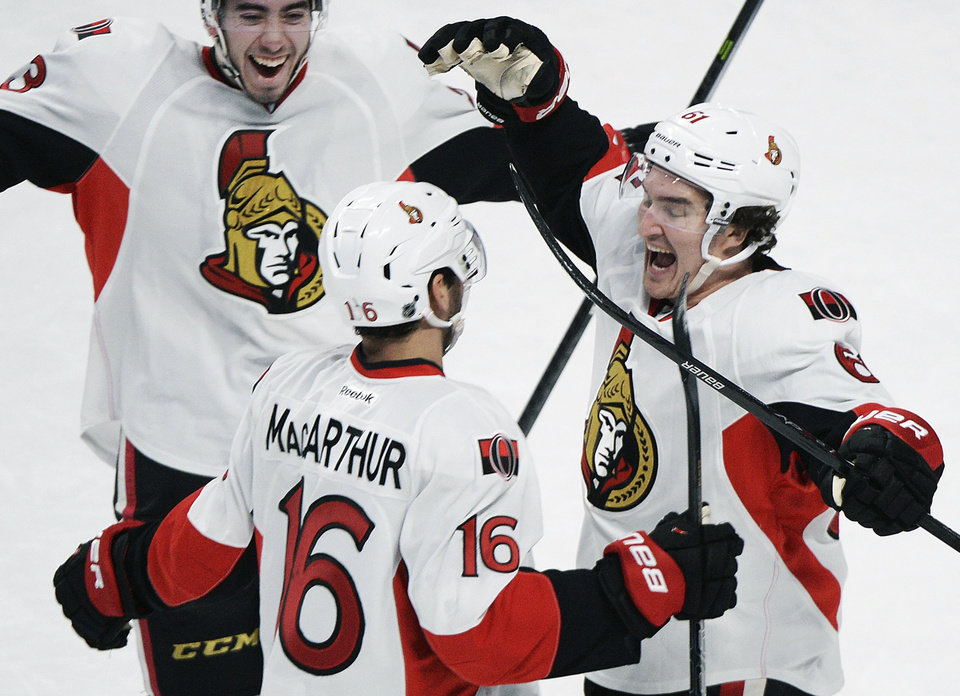 Photo - Ottawa Senators' Clarke MacArthur (16) celebrates with teammates Mika Zibanejad, left, and Mark Stone after MacArthur scored against the Montreal Canadiens during an overtime period of an NHL hockey game in Montreal, Saturday, Jan. 4, 2014. (AP Photo/The Canadian Press, Graham Hughes)