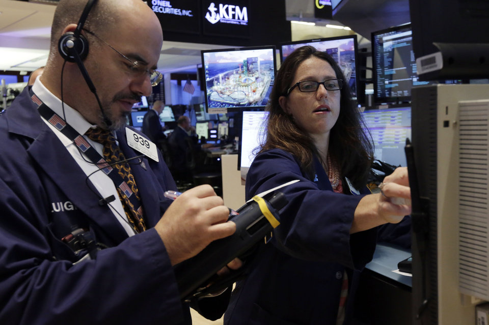 Photo - Trader Luigi Muccitelli, left, works with specialist Allison Gamba on the floor of the New York Stock Exchange, Monday, Aug. 4, 2014. U.S. stocks are opening mostly higher as the market recovers from a two-day slide last week. (AP Photo/Richard Drew)