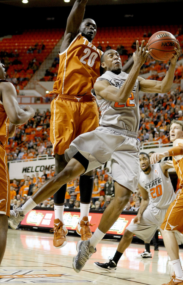 Photo - Oklahoma State's Markel Brown (22) goes past Texas' Alexis Wangmene (20) during an NCAA college basketball game between Oklahoma State University (OSU) and the University of Texas (UT) at Gallagher-Iba Arena in Stillwater, Okla., Saturday, Feb. 18, 2012. Oklahoma State won 90-78. Photo by Bryan Terry, The Oklahoman