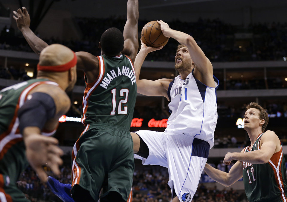 Milwaukee Bucks' Drew Gooden, Luc Richard Mbah a Moute (12) and Mike Dunleavy (17) defend as Dallas Mavericks' Dirk Nowitzki (41) shoots in the second half of an NBA basketball game Tuesday, Feb. 26, 2013, in Dallas. The Bucks won 95-90. (AP Photo/Tony Gutierrez)