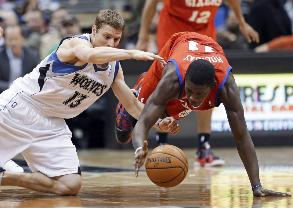 Photo - Minnesota Timberwolves' Luke Ridnour, left, and Philadelphia 76ers' Jrue Holiday scramble for the loose ball in the second half of an NBA basketball game Wednesday, Feb. 20, 2013, in Minneapolis. The Timberwolves  won 94-87. Holiday scored 16 points. (AP Photo/Jim Mone)