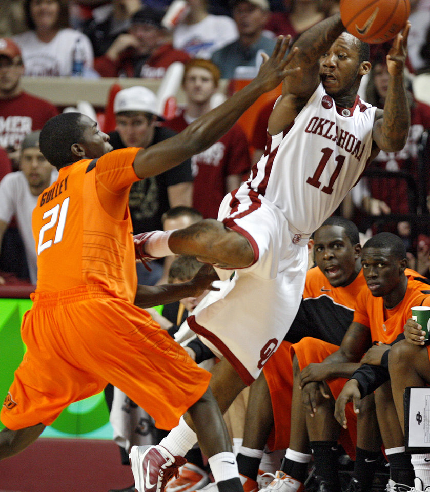 Photo - OU's Tommy Mason-Griffin (11) saves a turnover in front of OSU's Fred Gulley (21) during the first half of the college bedlam basketball game between The University of Oklahoma Sooners (OU) and Oklahoma State University University Cowboys (OSU) at the Lloyd Noble Center on Monday, Jan. 11, 2010, in Norman, Okla.