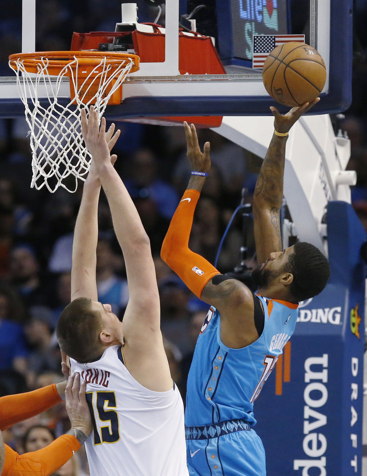 Photo - Oklahoma City Thunder forward Paul George, right, shoots in front of Denver Nuggets center Nikola Jokic (15) in the first half of an NBA basketball game Friday, March 29, 2019, in Oklahoma City. (AP Photo/Sue Ogrocki)