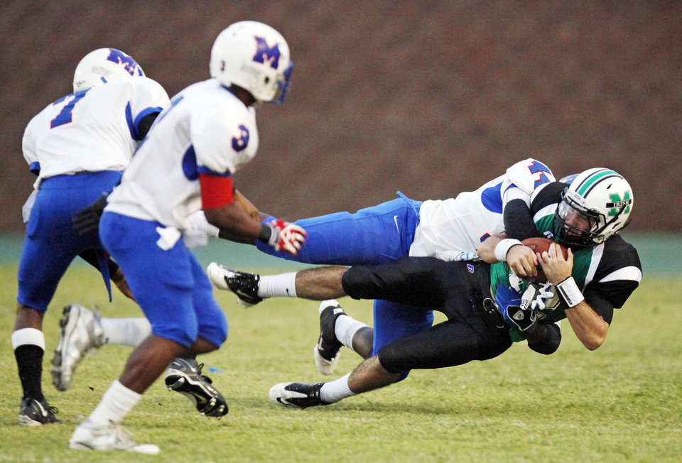 Photo - Larry Lambeth (44) of Millwood takes down Camden Tharp (12) of Bishop McGuinness next to Cameron Batson (3) and Malcom Scales (7) during a high school football game between Millwood and Bishop McGuinness at Bishop McGuinness Catholic High School in Oklahoma City, Friday, Sept. 16, 2011. Photo by Nate Billings, The Oklahoman
