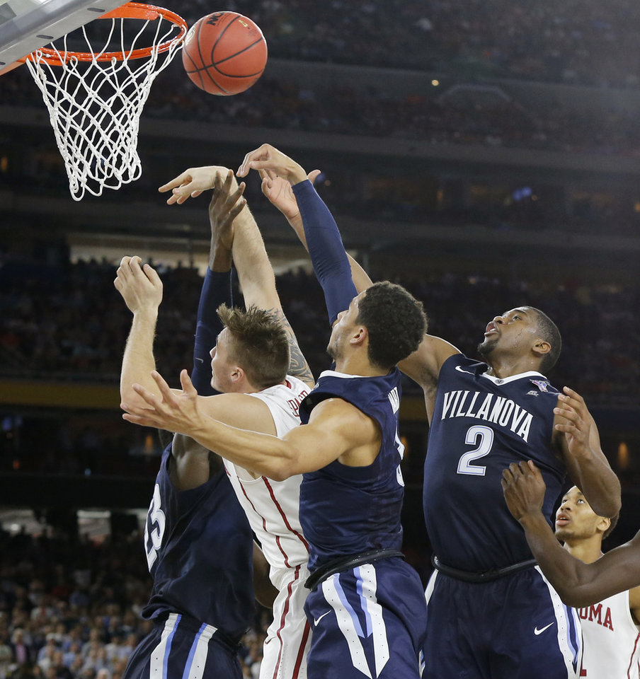 Photo - Oklahoma's Ryan Spangler (00) is defended by Villanova's Daniel Ochefu (23), Josh Hart (3) and Kris Jenkins (2) during the national semifinal between the Oklahoma Sooners (OU) and the Villanova Wildcats in the Final Four of the NCAA Men's Basketball Championship at NRG Stadium in Houston, Saturday, April 2, 2016. Photo by Nate Billings, The Oklahoman