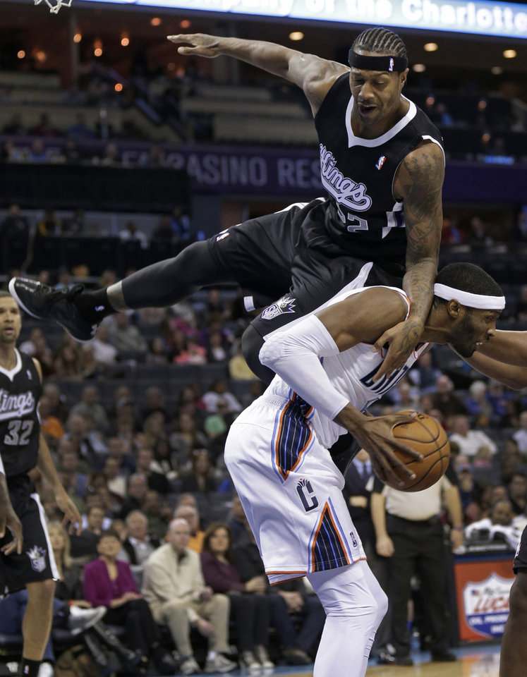 Photo - Sacramento Kings' Francisco Garcia, top, falls over Charlotte Bobcats' Hakim Warrick, bottom, during the first half of an NBA basketball game in Charlotte, N.C., Saturday, Jan. 19, 2013. (AP Photo/Chuck Burton)