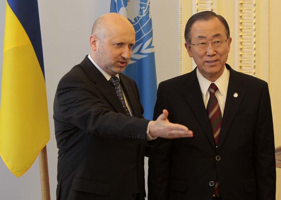 Photo - Acting Ukrainian President Oleksandr Turchynov, left, welcomes U.N. Secretary-General Ban Ki-moon during a meeting in Kiev, Ukraine, Friday, March 21, 2014. Russian President Vladimir Putin completed his annexation of Crimea on Friday, signing a law making the Black Sea peninsula part of Russia just as Ukraine itself sealed a deal pulling it closer into Europe's orbit. (AP Photo/Sergei Chuzavkov)