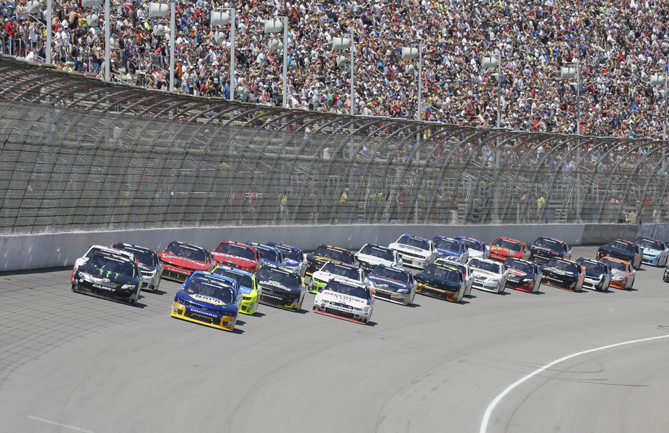 Photo - Drivers Chase Elliott, front right, and Kyle Busch, front left, lead the pack through the first turn during the NASCAR Nationwide series auto race at Michigan International Speedway in Brooklyn, Mich., Saturday, June 14, 2014. (AP Photo/Carlos Osorio)