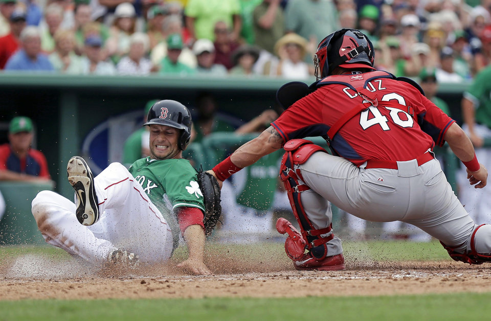 Photo - Boston Red Sox Daniel Nava, left, is safe at the plate as he avoids the tag of St. Louis Cardinals catcher Tony Cruz (48) in the fifth inning inning of an exhibition baseball game in Fort Myers, Fla., Monday, March 17, 2014. (AP Photo/Gerald Herbert)