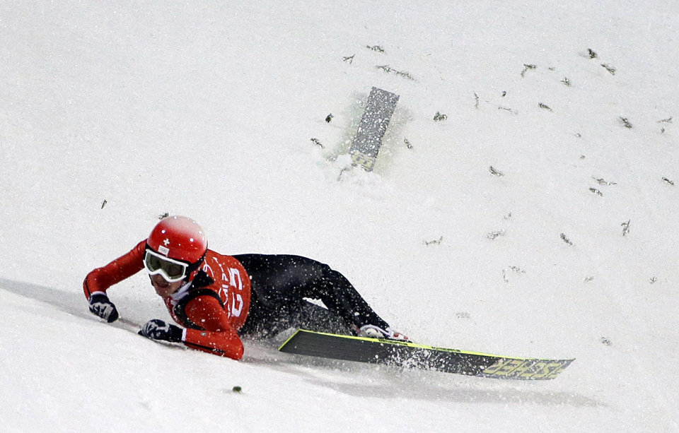 Photo - Switzerland's Simon Ammann crashes during a training session for the men's large hill ski jumping at the 2014 Winter Olympics, Thursday, Feb. 13, 2014, in Krasnaya Polyana, Russia. (AP Photo/Gregorio Borgia)