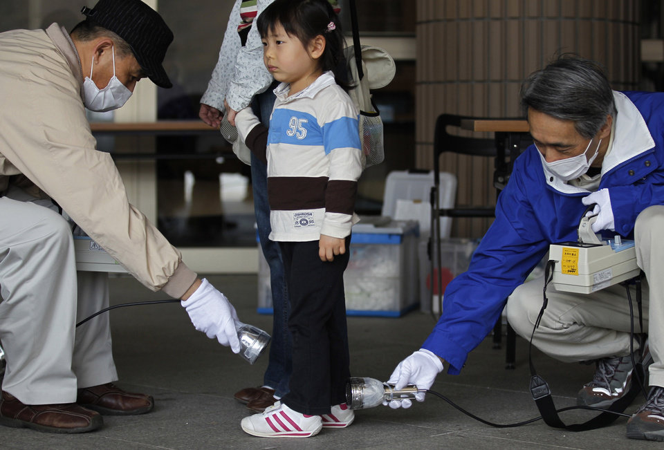FILE - In this April 16, 2011 file photo, Wakana Nemoto, 3, standing next to her mother Naoko, receives a radiation exposure screening outside an evacuation center in Fukushima, northeastern Japan. People exposed to the highest doses of radiation during the Fukushima nuclear plant disaster in 2011 may have a slightly higher risk of cancer that is so small it probably won�t even be detectable, according to a new report from the World Health Organization released on Thursday Feb. 28, 2013. (AP Photo/Hiro Komae, File)