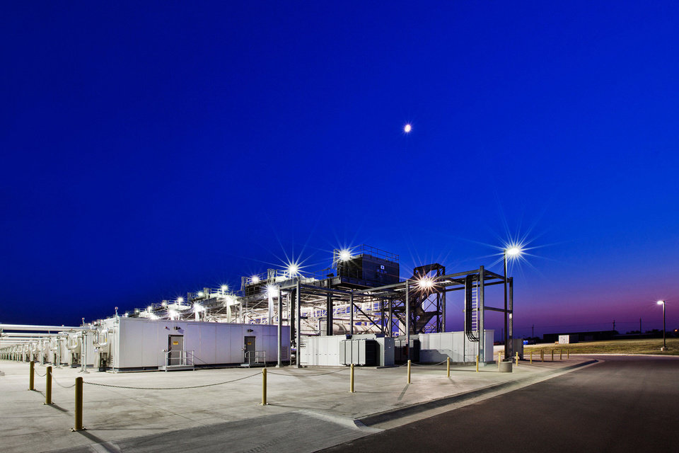 Photo - Bright lights and the moon light light up Google's data center in Pryor. These modular units provide cooling for a portion of the center.