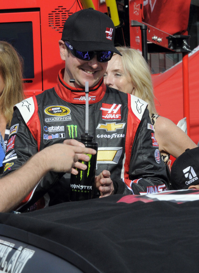 Photo - Kurt Busch gets a drink before getting into his car before the start of the NASCAR Sprint Cup series Coca-Cola 600 auto race at Charlotte Motor Speedway in Concord, N.C., Sunday, May 25, 2014. Busch finished sixth in the Indianapolis 500 earlier. (AP Photo/Mike McCarn)