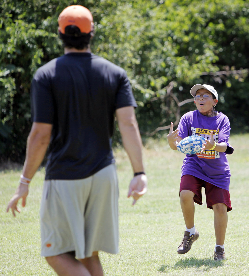 Photo - Camper Emilio Valdez, 11, right, tries to catch a pass from OSU quarterback Zac Robinson at the American Cancer Society's Camp Live-A-Dream in Guthrie, Okla., Wednesday, June 17, 2009. Photo by Nate Billings, The Oklahoman