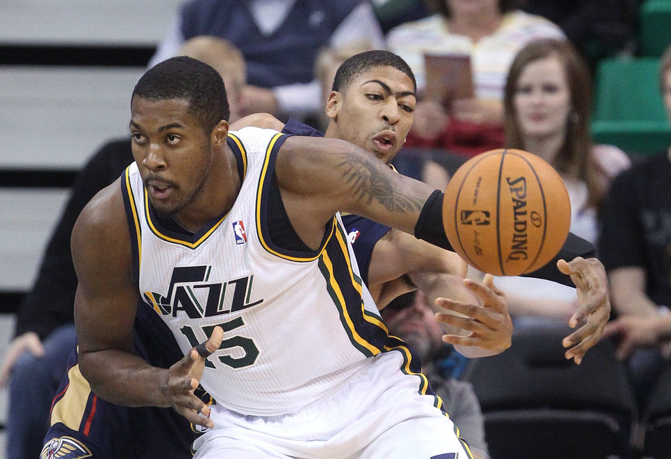 Photo - New Orleans Pelicans' Anthony Davis, rear, knocks the ball away from Utah Jazz's Derrick Favors (15) in the first quarter during an NBA basketball game Wednesday, Nov. 13, 2013, in Salt Lake City.  (AP Photo/Rick Bowmer)