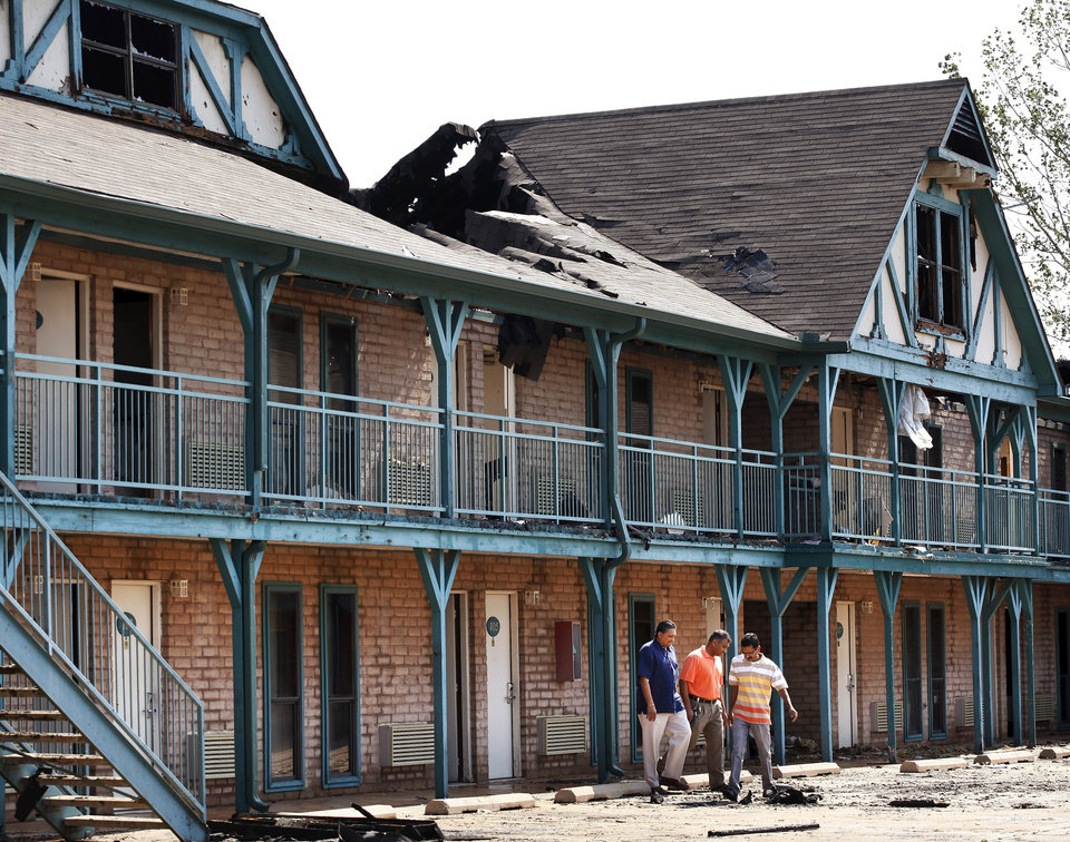 Three men who said they were friends of the owner of the business survey  damage to one wing of  the Stratford House Inns at 3020 S. Broadway in Edmond after a pre-dawn blaze destroyed the heavily damaged the buildings on  Wednesday, May  30,  2012,  Photo by Jim Beckel, The Oklahoman