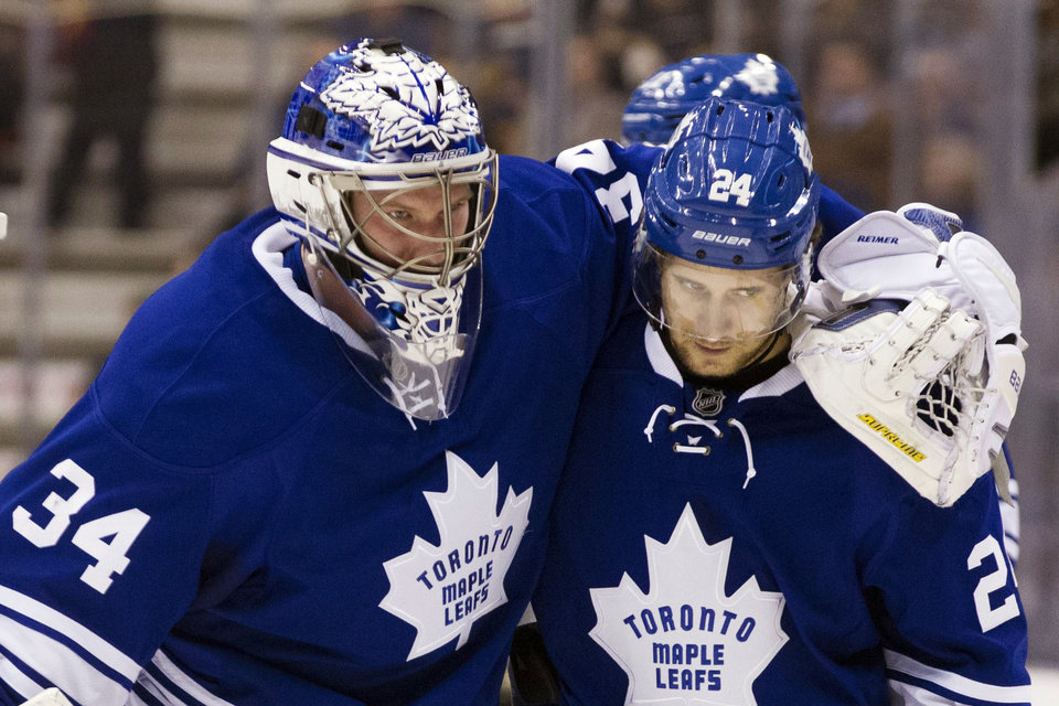 Photo - Toronto Maple Leafs goaltender James Reimer (34) is helped off the ice by John-Michael Liles during the second period of their NHL hockey game against the Philadelphia Flyers, Monday, Feb. 11, 2013, in Toronto. (AP Photo/The Canadian Press, Chris Young)