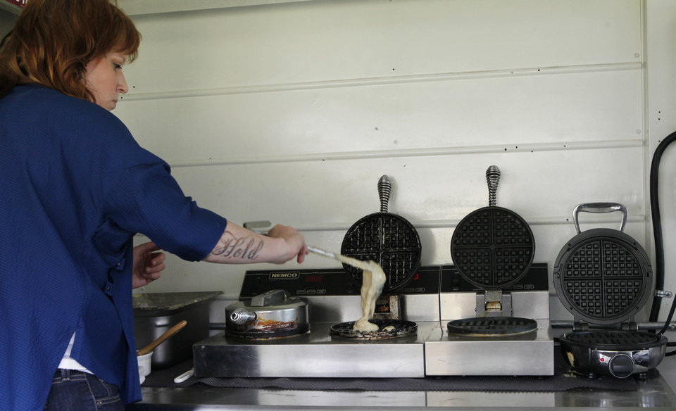 Tara Taylor pours batter into a waffle iron in the Waffle Champion truck. <strong>David McDaniel - The Oklahoman</strong>