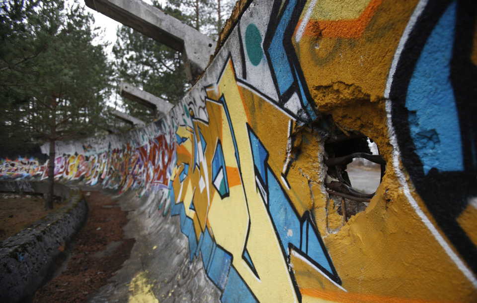 Photo - In this picture taken on Friday, Feb. 21, 2014, the bobsleigh track damaged by artillery fire is painted with graffiti at Mt. Trebevic near Bosnian capital of Sarajevo. Wartime destruction and negligence have turned most of Sarajevo's 1984 Winter Olympic venues into painful reminders of the city's golden times. The world came together in the former Yugoslavia in 1984 after the West had boycotted the 1980 Olympics in Moscow and Russia boycotted the 1984 Summer Games in Los Angeles. Just eight years later, the bobsleigh and luge track on Mount Trbevic was turned into an artillery position from which Bosnian Serbs pounded the city for almost four years. Today, the abandoned concrete construction looks like a skeleton littered with graffiti. (AP Photo/Amel Emric)
