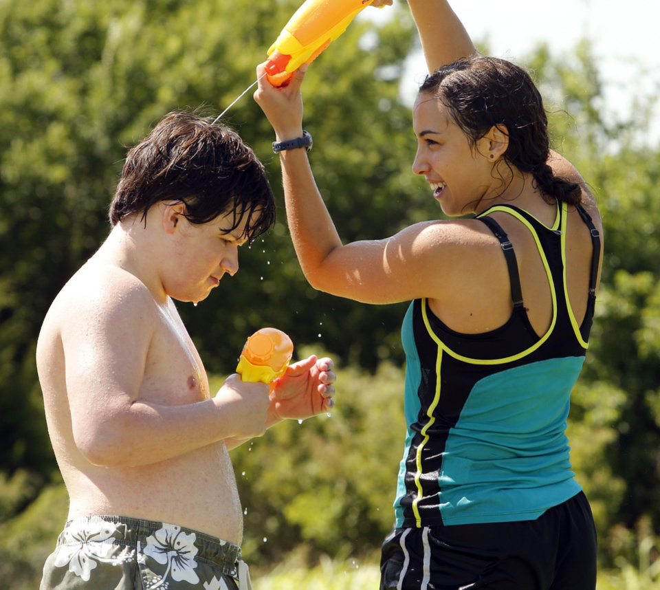 Photo -  Volunteer Taylor Cannon and camper Nolan Miles, 16, play water games at Camp ClapHans, an outreach program of the J.D. McCarty Center in Norman. PHOTO BY STEVE SISNEY, THE OKLAHOMAN   STEVE SISNEY -