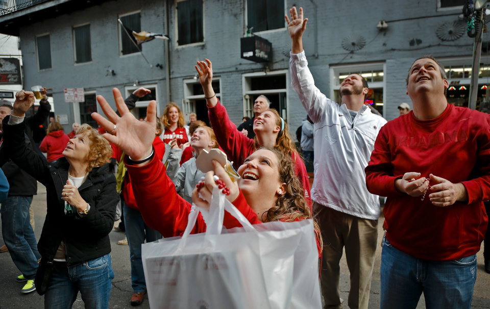 Photo - Sooner fan Claire Hosek, center, tries to catch beads thrown from the balconies on Bourbon Street before the start of the NCAA football BCS Sugar Bowl game between the University of Oklahoma Sooners (OU) and the University of Alabama Crimson Tide (UA) at the Superdome in New Orleans, La., Thursday, Jan. 2, 2014.  .Photo by Chris Landsberger, The Oklahoman