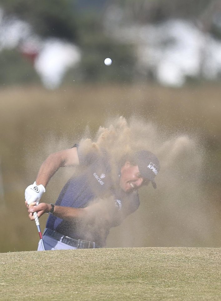 Phil Mickelson of the United States plays out of a bunker on the 15th hole during the third round of the British Open Golf Championship at Muirfield, Scotland, Saturday July 20, 2013. (AP Photo/Scott Heppell)
