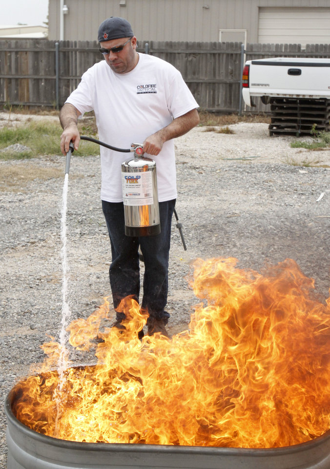 "Coldfire representative Ray Geissler demonstrates how quickly his company's  product can extinguish a gasoline fire during a demonstration of ""Coldfire"" at the Yukon Fire Dept. in Yukon, OK, Thursday, October 11, 2012,  By Paul Hellstern, The Oklahoman"