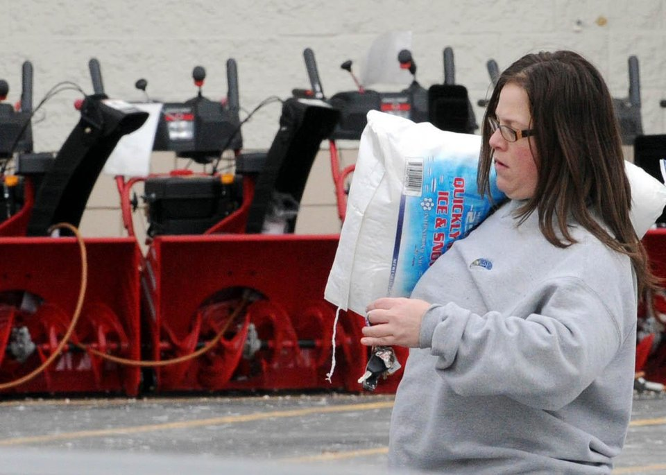 Sue Corsentino walks to her vehicle with a bag of salt in preparation for the coming snow storm Thursday at Lowe's in Greenwich Township, N.J.   A winter storm that is heading for New England will be bringing snow, sleet and rain to Pennsylvania along the way.   (AP Photo/Express-Times,STEPHEN FLOOD)