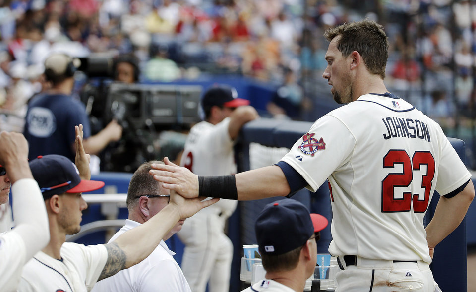 Photo - Atlanta Braves' Chris Johnson, right, high-fives teammates for scoring Justin Upton off a single as he returns to the dugout after getting out on a double play in the fourth inning of a baseball game against the Arizona Diamondbacks, Sunday, July 6, 2014, in Atlanta. (AP Photo/David Goldman)