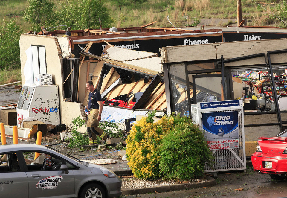 An Oklahoma City firefighter looks at damage Monday at a Love's Travel Stop at Interstate 40 and Choctaw Road after a tornado ripped off the building's roof.  Photo by Jim Beckel, The Oklahoman
