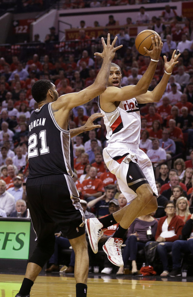Photo - Portland Trail Blazers' Nicolas Batum, right, drives to the basket as San Antonio Spurs' Tim Duncan (21) defends in the first quarter during Game 4 of a Western Conference semifinal NBA basketball playoff series Monday, May 12, 2014, in Portland, Ore. (AP Photo/Rick Bowmer)