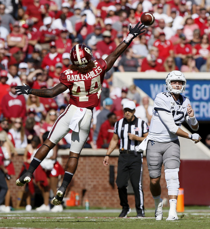Photo - Oklahoma's Brendan Radley-Hiles (44) reaches for the ball as West Virginia's Austin Kendall (12) throws a pass during a college football game between the University of Oklahoma Sooners (OU) and the West Virginia Mountaineers at Gaylord Family-Oklahoma Memorial Stadium in Norman, Okla, Saturday, Oct. 19, 2019. Oklahoma won 52-14. [Bryan Terry/The Oklahoman]