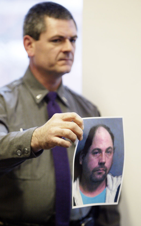 In this Jan. 2, 2013 photo, New York State Police Lt. John Durling shows a picture of 39-year-old serial burglary suspect John W. Suddard, Jr. during a news conference at Hudson Falls Village Court in Hudson Falls, N.Y. Few clues exist pointing to the owners of the roughly 30,000 items discovered after Suddard�s recent arrest. So police are taking the novel step of displaying the items at the local high school Wednesday night, Jan. 9, 2013. (AP Photo/The Post-Star, Derek Pruitt)