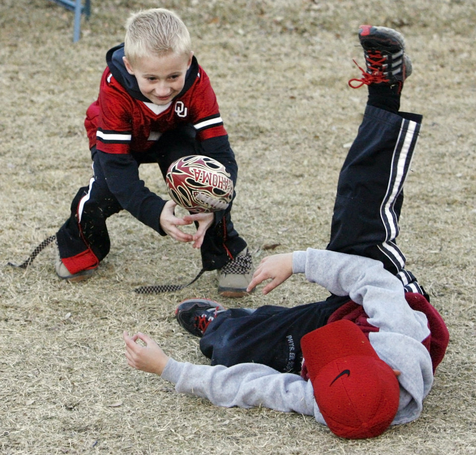 Photo - OU fans Jachob Washington, 8, of Snow, Okla., and Colby Carter, 6, of Okeene, Okla., play football outside the stadium before the college football game between the University of Oklahoma Sooners and Texas Tech University at Gaylord Family -- Oklahoma Memorial Stadium in Norman, Okla., Saturday, Nov. 22, 2008. Carter and Washington are cousins. BY NATE BILLINGS, THE OKLAHOMAN