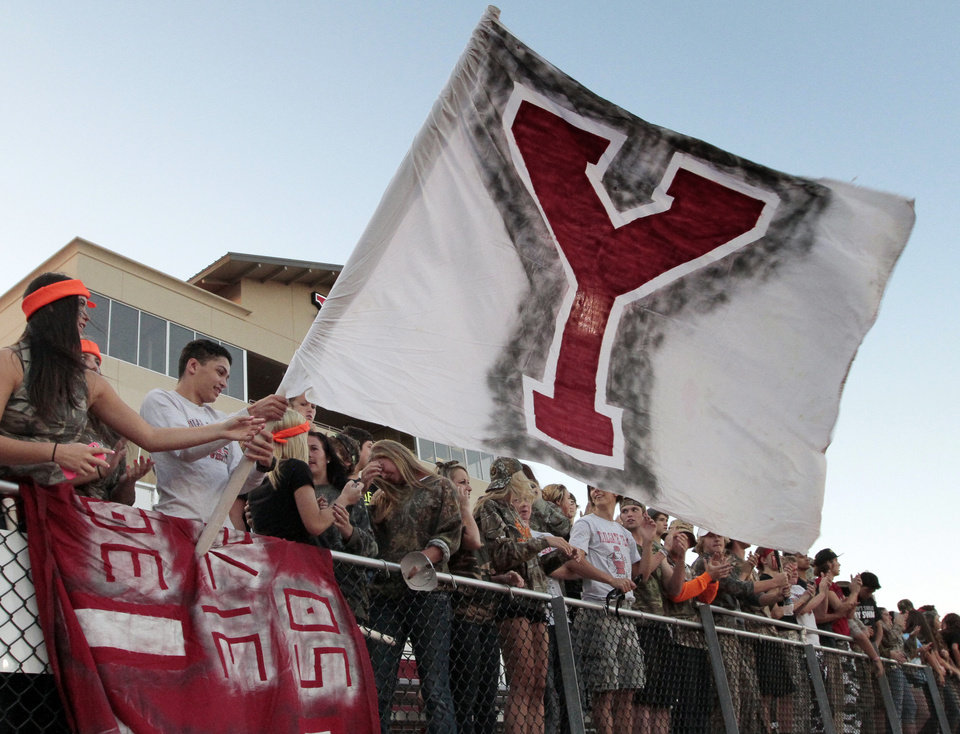 Photo - Yukon fans unfurl a flag in the wind as Edmond North plays Yukon in high school football on Thursday, Oct. 10, 2013, in Yukon Okla. Photo by Steve Sisney, The Oklahoman