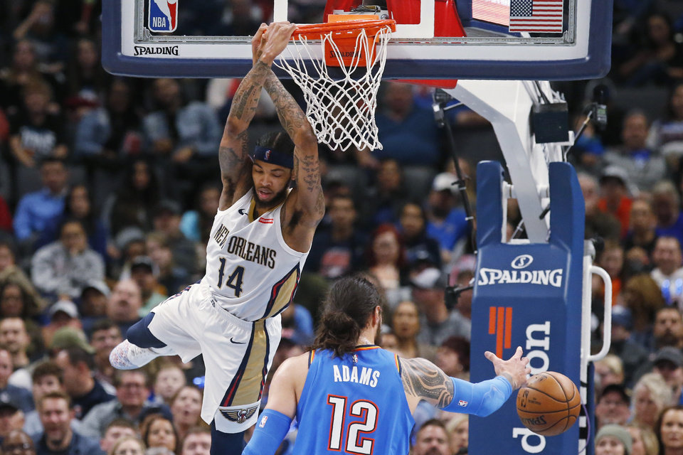 Photo - New Orleans Pelicans forward Brandon Ingram (14) hangs from the basket after dunking in front of Oklahoma City Thunder center Steven Adams (12) during the first half of an NBA basketball game Friday, Nov. 29, 2019, in Oklahoma City. [AP Photo/Sue Ogrocki]
