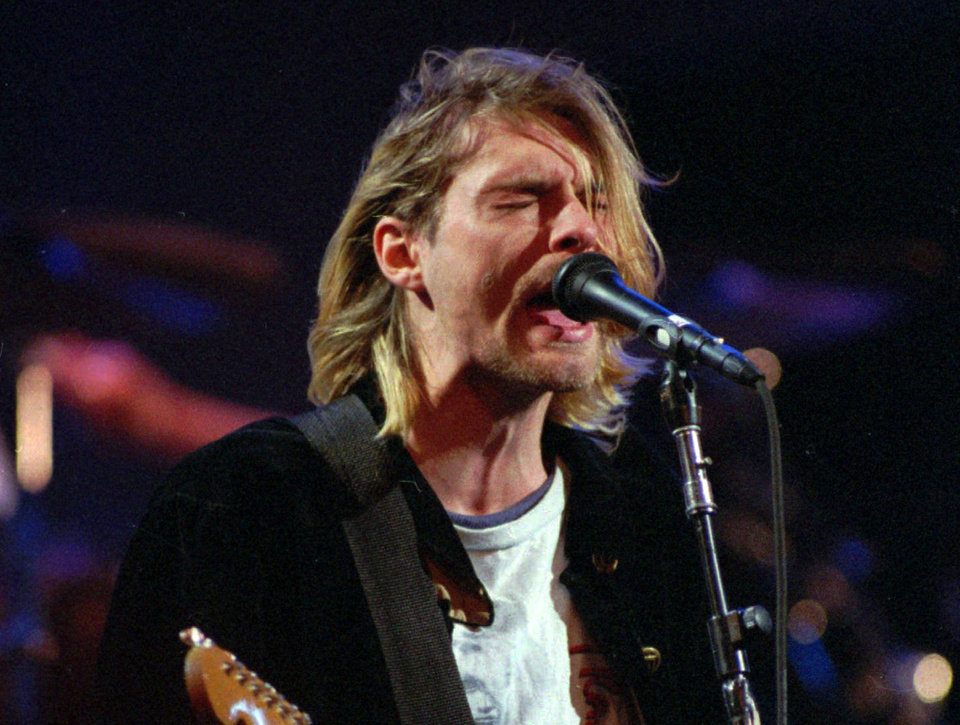 Photo - FILE - This Dec. 13, 1993 file photo shows Kurt Cobain of the Seattle band Nirvana performing in Seattle, Wash. It's been two decades since the Nirvana frontman took his own life yet he remains on in the thoughts of those he influenced and entertained. He's a touchstone for young musicians clutching guitars the world over and his story is a tale of both inspiration and caution. His influence still ripples across the surface of pop music and his shadow even looms in the hip-hop world where he's been a referenced by Jay Z, Kanye, Kendrick Lamar, Drake and Jay Electronica in various ways recently. (AP Photo/Robert Sorbo, file)