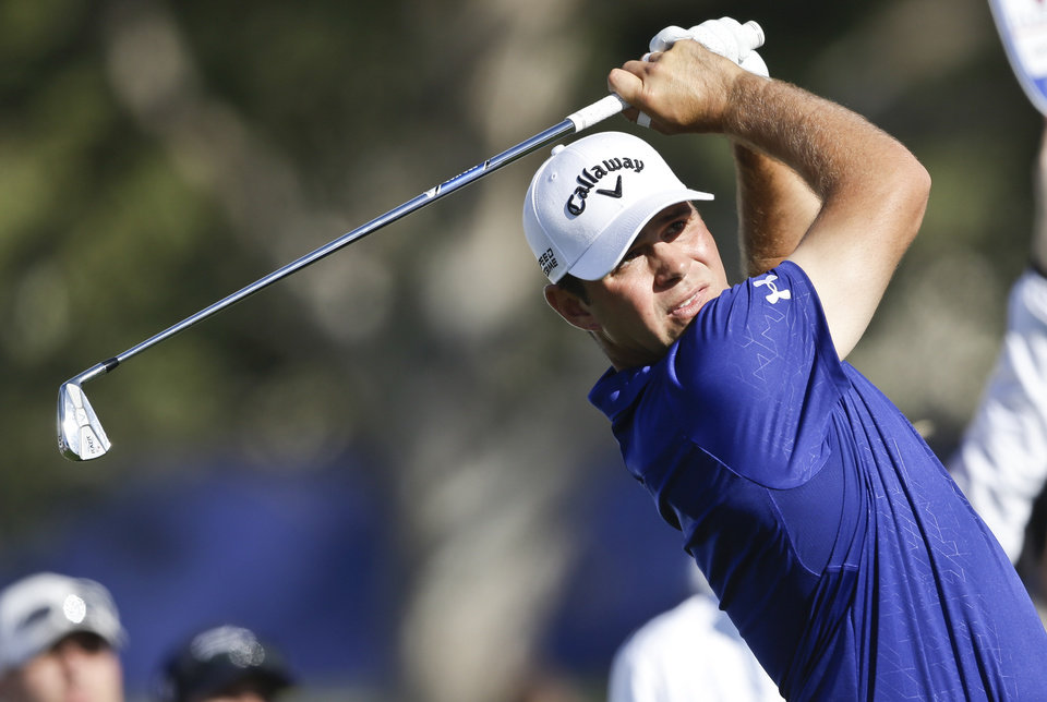 Photo - Gary Woodland watches his tee shot on the par-3 16th hole of the South Course at Torrey Pines during the third round of the Farmers Insurance Open golf tournament Saturday, Jan. 25, 2014, in San Diego. Woodland birdied the hole and leads the tournament at 8 under par. (AP Photo/Lenny Ignelzi)