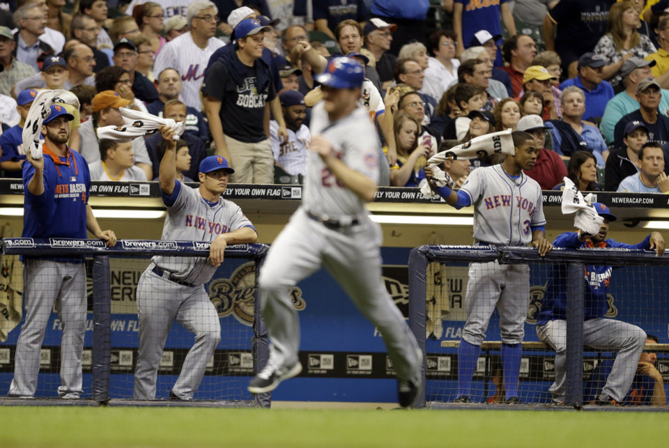 Photo - New York Mets players wave towels as Daniel Murphy scores on a hit by David Wright during the ninth inning of a baseball game Friday, July 25, 2014, in Milwaukee. (AP Photo/Jeffrey Phelps)