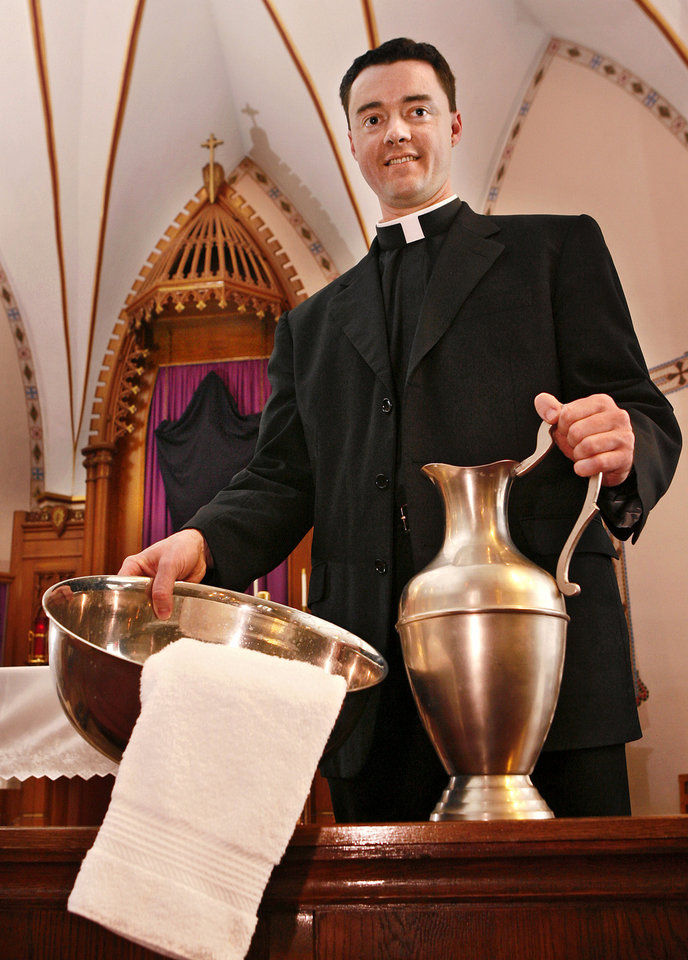 Photo - In this 2008 photo, the Rev. Stephen Hamilton displays items utilized for Holy Thursday the foot washing ritual. Hamilton has been appointed vocation director for the Archdiocese of Oklahoma City. He also will serve as pastor of St. Monica Catholic Church in Edmond beginning in summer.  Jim Beckel - The Oklahoman
