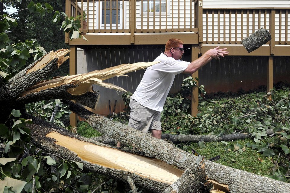 Photo -   Gary Davis tosses aside a section of a Tulip Poplar tree the fell behind a friend's house on Greenwood Drive in Lynchburg, Va., July 1, 2012. The tree fell between two houses, narrowly sparing both. (AP Photo/The News & Advance, Parker Michels-Boyce)
