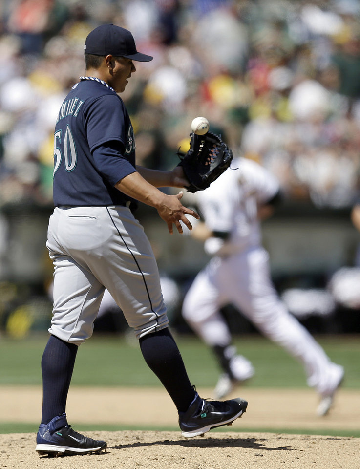 Photo - Seattle Mariners' Erasmo Ramirez tosses the ball in his glove after giving up a three-run home run to Oakland Athletics' Brandon Moss in the third inning of a baseball game Sunday, April 6, 2014, in Oakland, Calif. (AP Photo/Ben Margot)