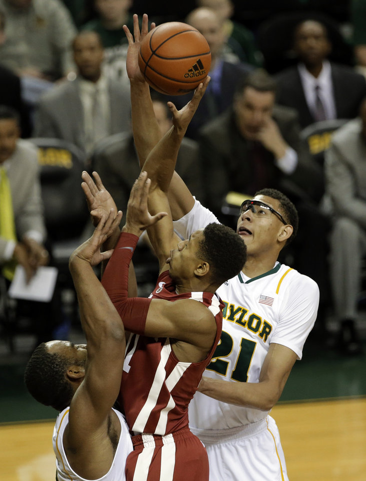 Photo - Oklahoma guard Isaiah Cousins (11) has his shot blocked by Baylor center Isaiah Austin (21) with help from Rico Gathers, bottom left, during the first half of an NCAA college basketball game Wednesday, Jan. 30, 2013, in Waco, Texas. (AP Photo/Tony Gutierrez)