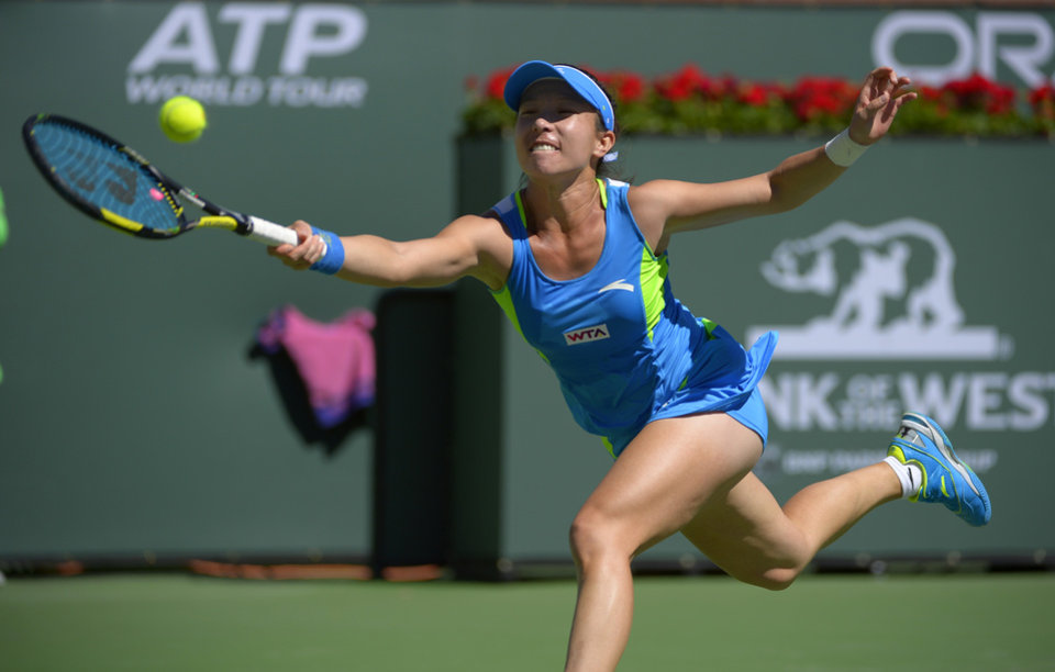 Photo - Zheng Jie, of China, returns a shot to Li Na, of China, during their match at the BNP Paribas Open tennis tournament, Saturday, March 8, 2014, in Indian Wells, Calif. (AP Photo/Mark J. Terrill)