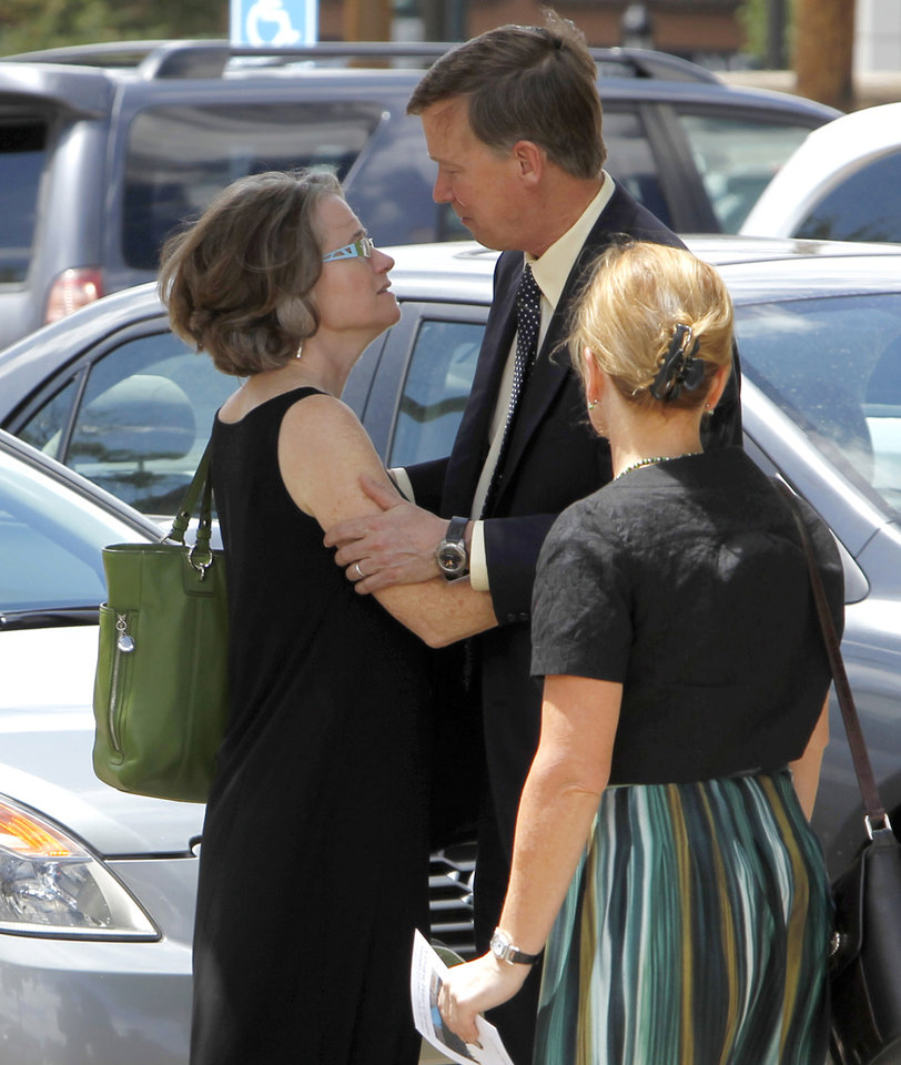 Photo -   Colorado Gov. John Hickenlooper hugs his wife Helen Thorpe as they leave a memorial service for Gordon Cowden at the Pathways Church in Denver on Wednesday, July 25, 2012. Cowden was one of 12 people killed, and over 50 wounded in a shooting attack early Friday at the packed theater during a showing of the Batman movie,