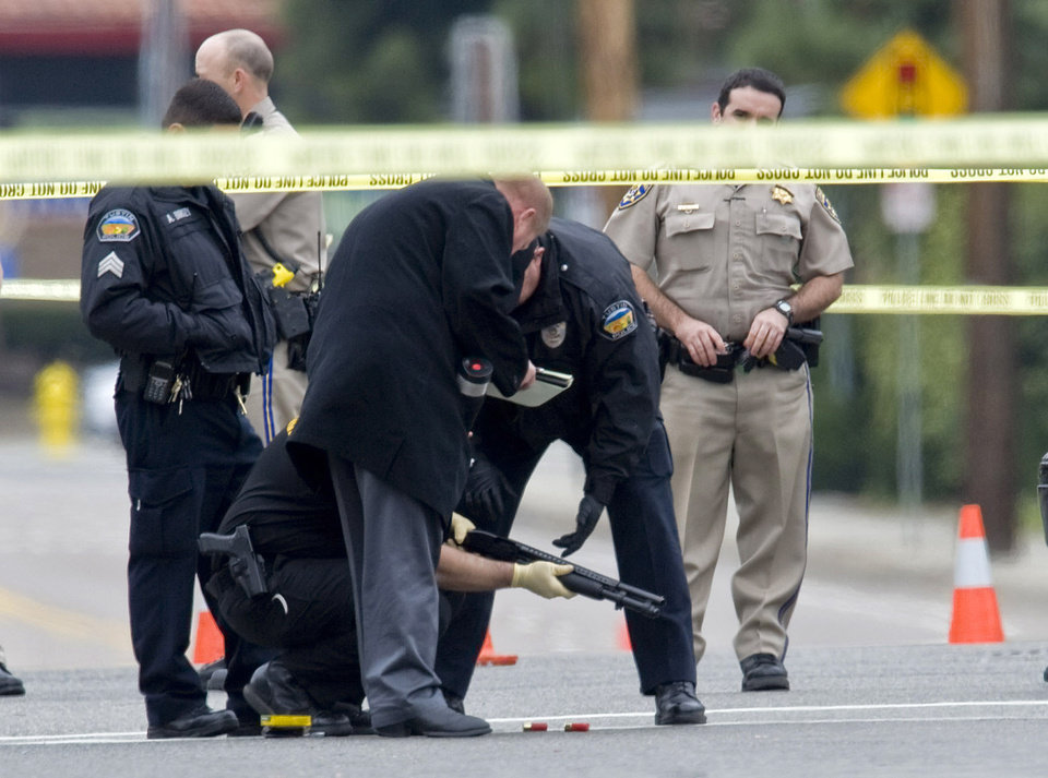 Photo - Police investigators examine a gun laying in the street at the intersection of Wanda Road and Katella Avenue in Orange, Calif., early Tuesday, Feb. 19, 2013 near where a body laid moments before. A shooting spree early Tuesday left three people dead and two others injured in Orange County, and the search for the gunman ended when he shot himself to death in a stolen car as police closed in, authorities said.(AP Photo/The Orange County Register, Mark Rightmire)   MAGS OUT; LOS ANGELES TIMES OUT