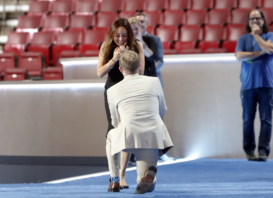 Photo - Andrew Binns kneels while proposing to Liz Hart on the main stage before the 2016 Democratic Convention, Sunday, July 24, 2016, in Philadelphia. The two work on production for the convention. (AP Photo/Paul Sancya)